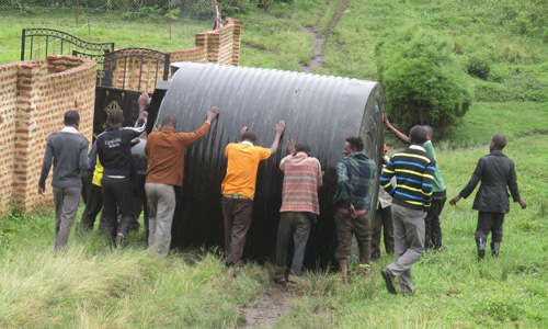 rolling large water tank to school before there was a proper track